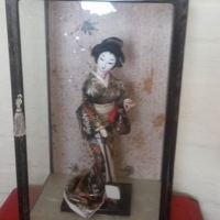 Chinese geisha doll in glass cabinet