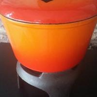 Orange cast iron fondue pot and stand.