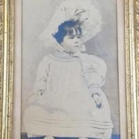 Vintage photo in frame, little girl in dress