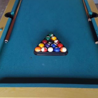 Pool table for sale with complete set of 8 balls and two sticks with few chalks