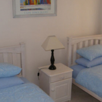 Whitewashed single beds with mattresses