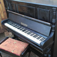 Dark wooden piano with chair