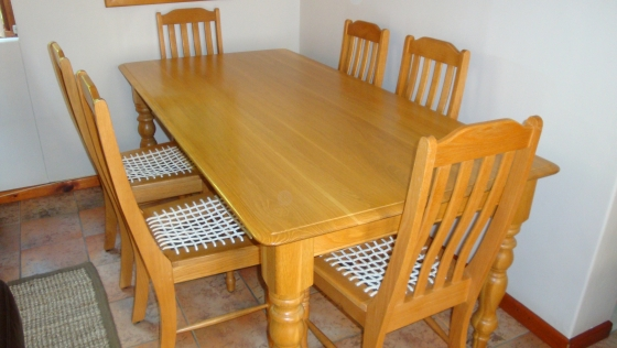 Dining Table in solid light oak and 6 high back chairs with riempie seats