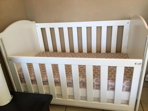 White wooden cot and mattress