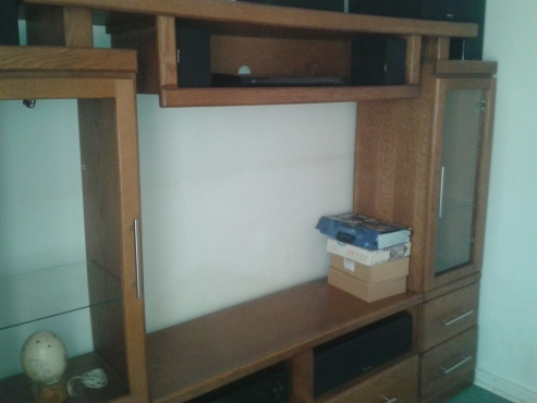 Wall unit big enough to fit 60 inch flat screen.  Super wood with oak finish.  Light fittings inside